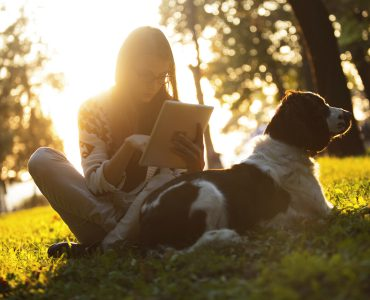 """alt=""""woman enjoying the sun outdoors in sunset with dog using tablet""""/>"""