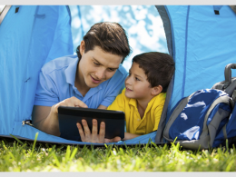 Two people in tent using a tablet