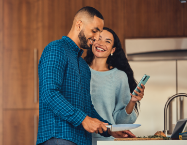 Man cooking while woman smiles and holds her phone.