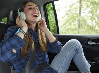 A young woman wearing headphones in the back of a car.