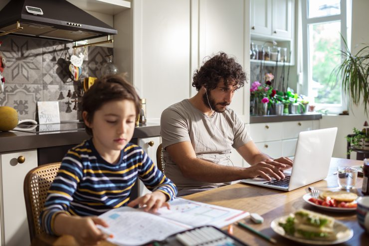 father and child in kitchen on computers using internet with Wi-Fi 6 technology